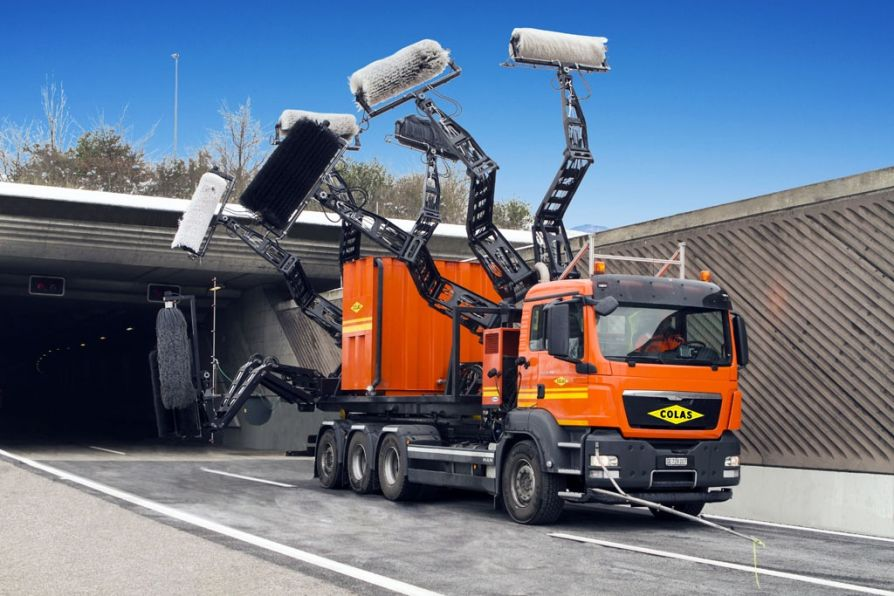 Unusual multi-armed machine Colas Suisse for washing of road tunnels